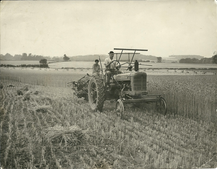 Binding Wheat in the Warren Field up Mill Lane in 1947.  Frank Randall on the Farmall Tractor, Doris Newbound on the Binder (Doris married George Randall the following year)