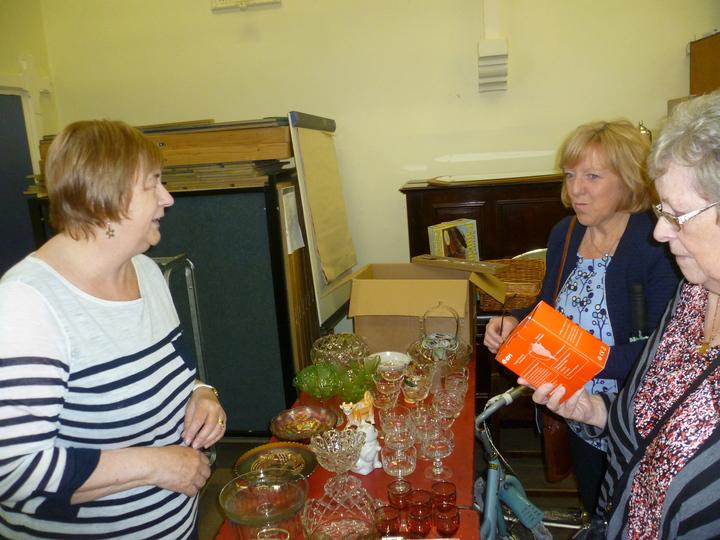 "Geraldine serves Linda & Margaret at the ""Bric-a-brac"" stall"
