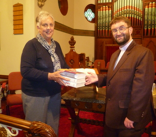 Marcus is presented with the gift of new Hymn Books by Mrs Christine Hind