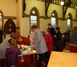 Members of the congregation queue for their piece of the pudding