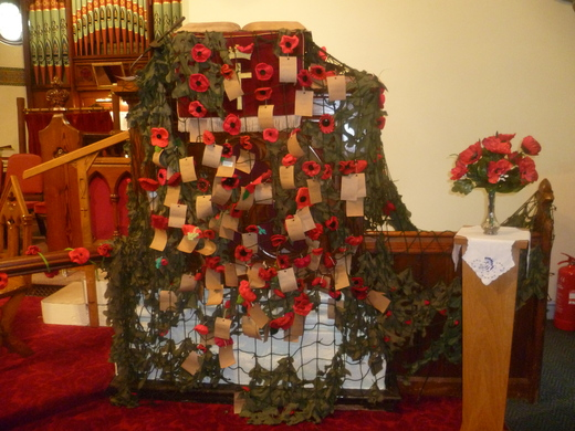 Poppies cascade from the Pulpit with names of servicemen who died in the war attached